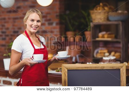 Portrait of a waitress holding two cups of coffees at the coffee shop