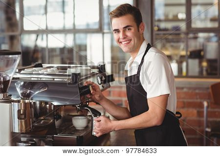 Portrait of smiling barista steaming milk at coffee machine at coffee shop