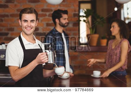 Portrait of smiling barista pouring milk into cup in front of customers at coffee shop