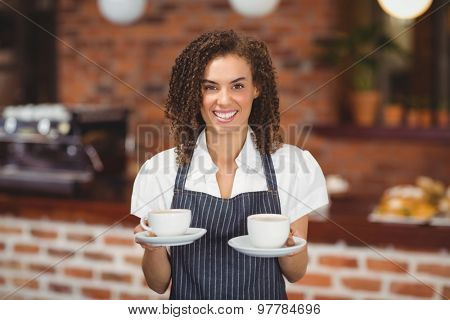 Portrait of smiling barista serving two cups of coffee at coffee shop