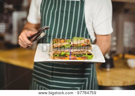 Close up of waiter holding a plate of sandwiches at the coffee shop