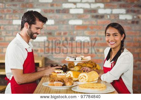 Portrait of waiters tidying up pastries on the counter at the coffee shop