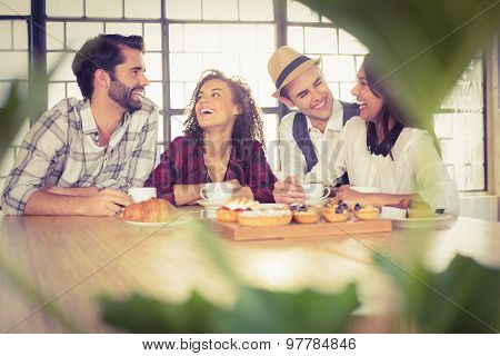 Laughing friends enjoying coffee and treats at coffee shop