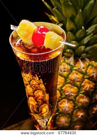Close up of champagne  cocktail with cherry and whole pineapple with leaves .