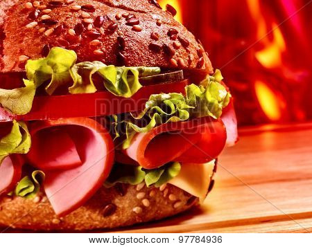Half of hamburger with ham on wooden board on background of fire.