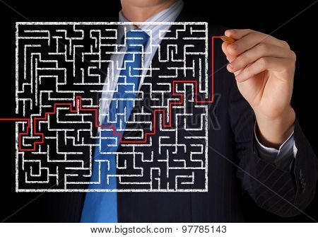 Close up view of businessman drawing way in labyrinth