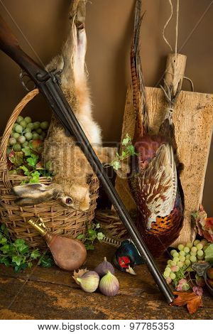 Autumn still life with hunting rifle, pheasant and hare