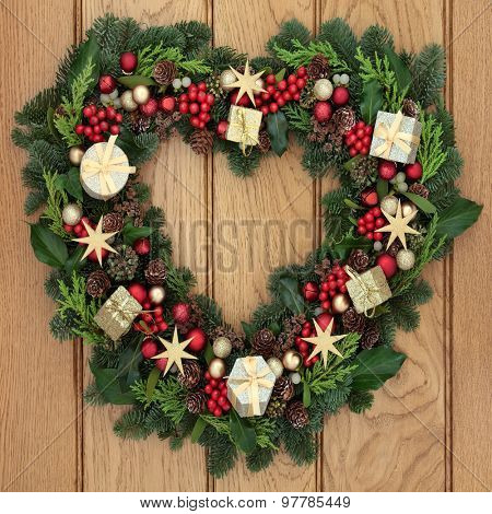 Christmas heart shaped wreath with red and gold bauble decorations, holly, mistletoe and greenery over oak front door background.