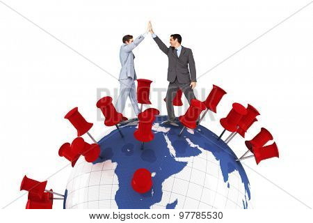 Businessmen high fiving against pins showing locations on earth