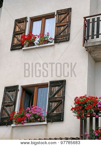 Mountain Home With Flowered Balcony With Geraniums In Summer