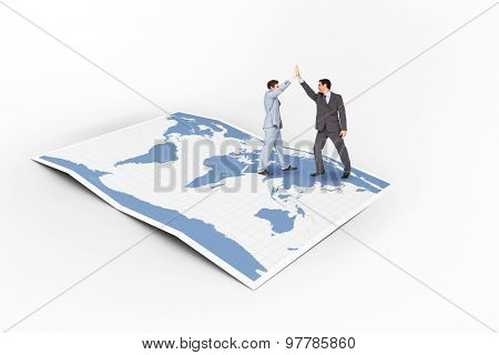 Businessmen high fiving against world map