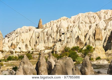 Detailed photo of vivid pink rock formations with caves from above in Cappadocia, Turkey