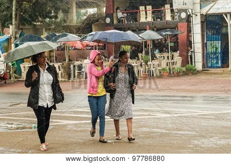Three Women With An Umbrella Walking On The Streets Of Addis In The Rain