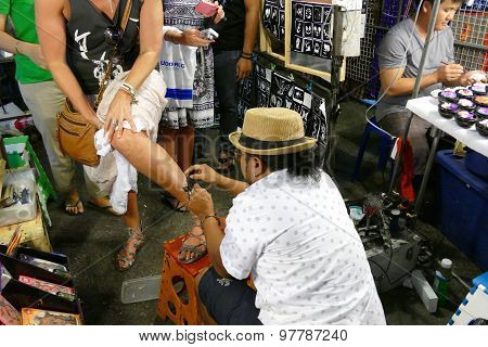 The Man Is Making Air Brush Tattoo On Tourist Leg At Night Market.