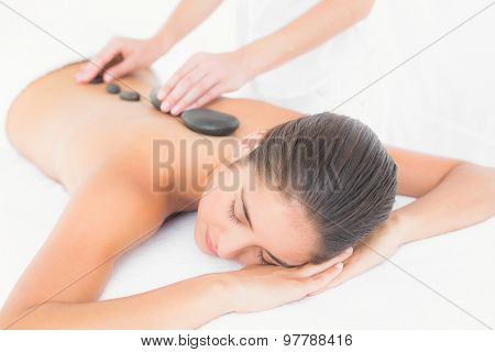 Beautiful brunette enjoying a hot stone massage at the health spa