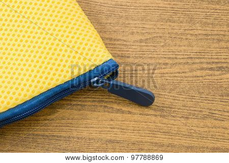 Yellow Bag With Blue Zipper On Wooden Board