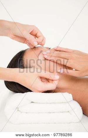 Close up view of hands threading beautiful womans eyebrow