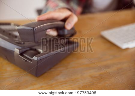 Hipster businessman answering the phone in his office