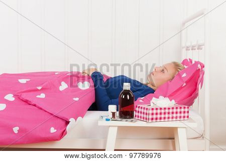 Sick teen girl laying in bed with medicine in front (focus on girl)