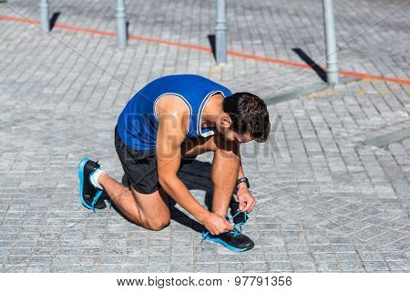 An handsome athlete doing his shoelaces on a beautiful day