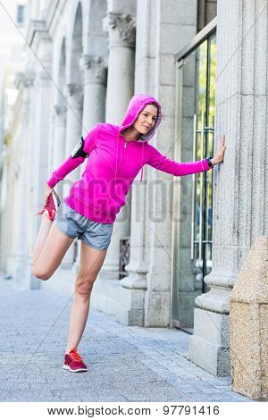 A woman wearing a pink jacket stretching on a sunny day