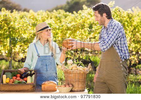 Happy farmer couple handing bread at the local market