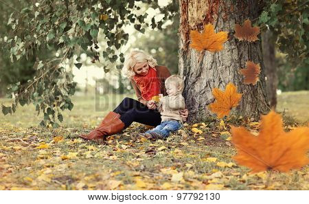 Happy Mom And Child Playing And Having Fun Together Sitting Under A Tree On A Warm Autumn Day, Flyin