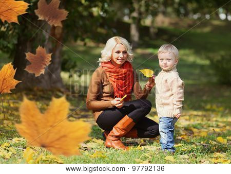 Happy Mom And Child Playing Together In Warm Autumn Day, Flying Yellow Maple Leaves