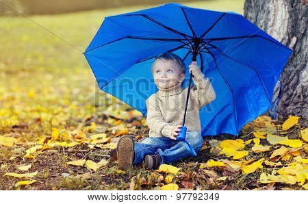 Portrait Of Cute Child With Umbrella Sitting On Yellow Leaves In Autumn Day