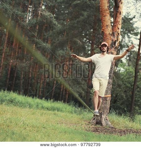 Sport, Leisure, Recreation And Healthy Active Lifestyle Concept - Man Slacklining Walking And Balanc