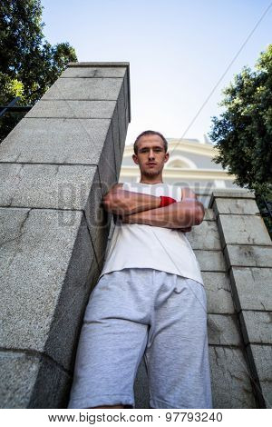 Portrait of extreme athlete standing next to wall with arms crossed in the city