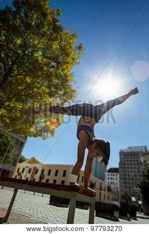 Athletic woman performing handstand and doing split on bench in the city