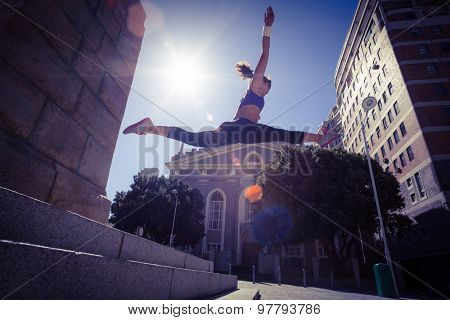 Athletic woman jumping off the stairs and doing split in the air in the city
