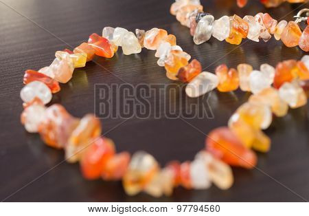 A Necklace Of Stone Beads On A Wooden Surface Close-up