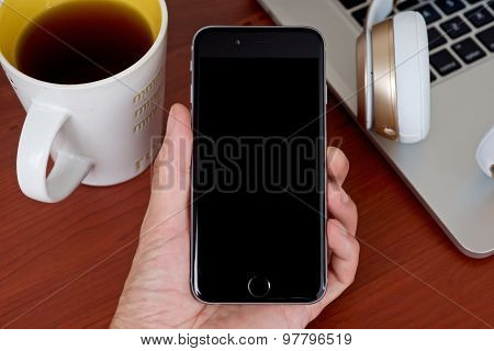 Hand Holding Mobile Phone With Coffee Table Background