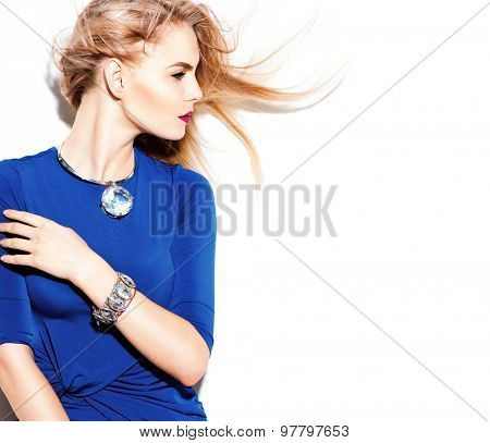 High Fashion model girl wearing blue dress portrait. Blowing blonde Hair. Beauty young woman with accessories staying near the wall. Perfect makeup