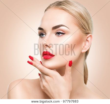 Beautiful fashion model girl with blond hair. Red lipstick and nails. Portrait of glamour woman with bright makeup over beige background. Beauty female face close up with perfect make up and manicure