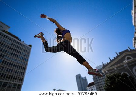 Athletic woman jumping in the air in the city
