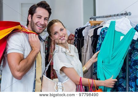 Portrait of smiling couple browsing clothes in clothing store