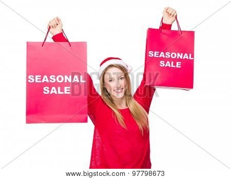 Woman with Christmas hat and hold up the paper bag showing seasonal sale