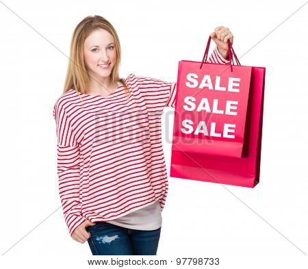 Woman holding with shopping bag and showing three sale word