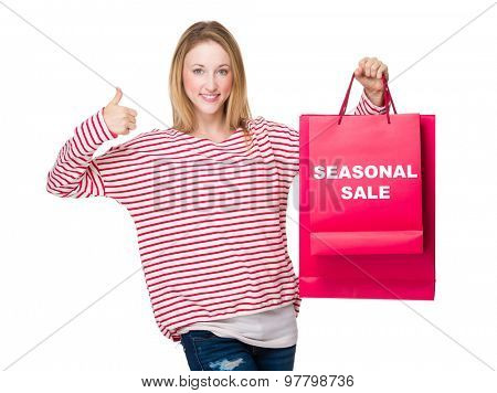 Woman hand thumb up gesture and hold with shopping bag showing seasonal sale