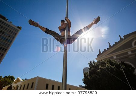 Athletic woman doing gymnastics on street sign in the city
