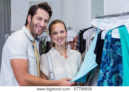 Portrait of smiling couple looking at clothes in clothing store