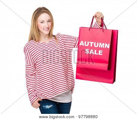 Woman holding with shopping bag and showing autumn sale