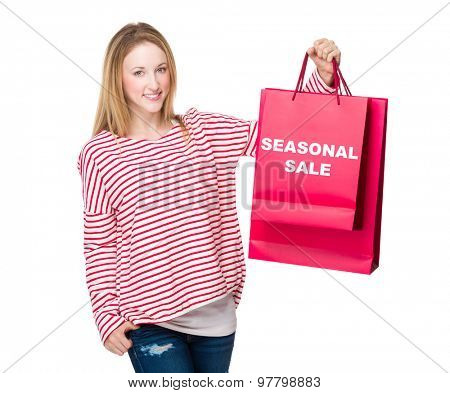 Woman holding with shopping bag and showing seasonal sale