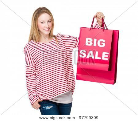 Woman holding with shopping bag and showing big sale