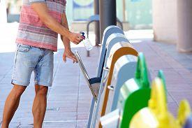 picture of recycle bin  - Male putting plastic bottle in recycling bin - JPG