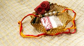 image of rakhi  - rakhi wrist band with the traditional tilak and rice in a golden mesh holder - JPG
