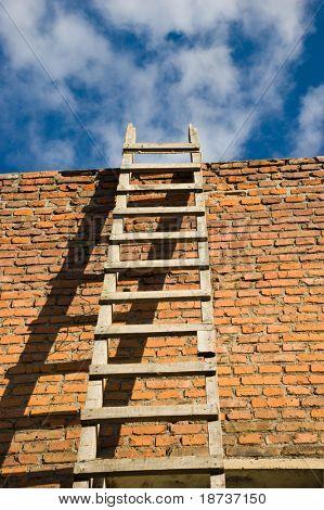 escalera de madera en la pared naranja